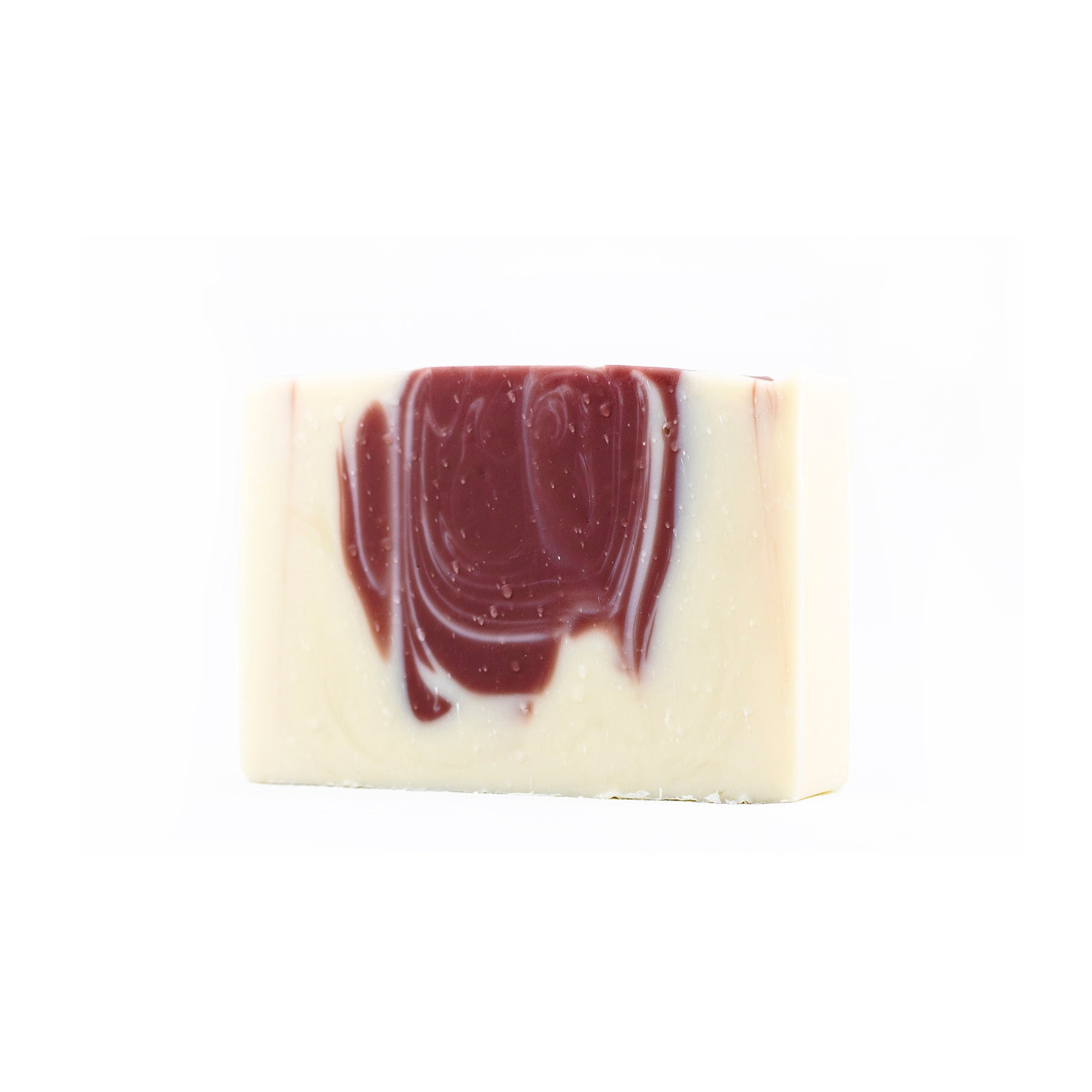 A white bar of soap with a maroon drop swirl in it centre on a white back drop.