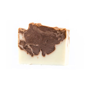 Brown and white swirled bar of soap with textured top on a white background.