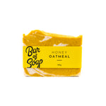 Load image into Gallery viewer, A soft yellow and white mixed in uneven layers of a bar of soap. It is labeled with a yellow Honey Oatmeal Bar of Soap label.