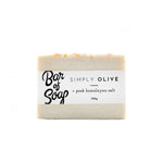 A simple and white pure olive oil bar of soap with little speck of pink himalayan salt throughout. The bar is also topped with some larger pieces of Himalayan salt. The bar of soap is wrapped with a Simply Olive + Himalayan Soap Bar of Soap label.