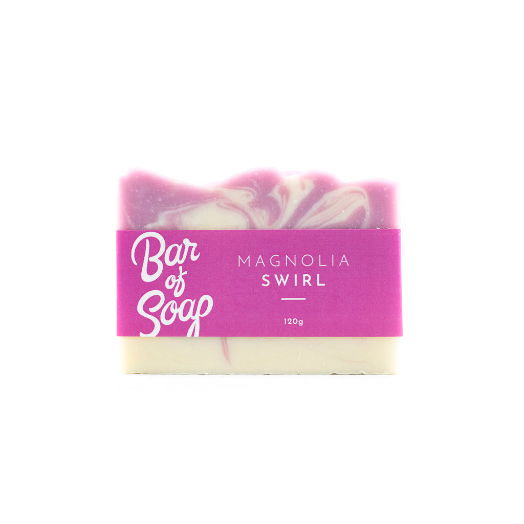 A pin and white Bar of Soap with a Magnolia Swirl Bar of soap label