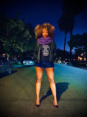"""American soprano Shauna L. Howard standing in the middle of a Los Angeles street wearing a purple Fierce Stitch infinity scarf, a short that says """"Keep calm or I will use my opera voice"""" tshirt, a leather jacket, jean shorts, and rainbow stilettos."""
