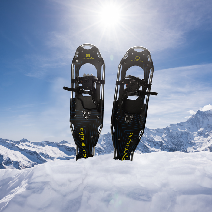 Pair of Outbound snowshoes on snow with landscape