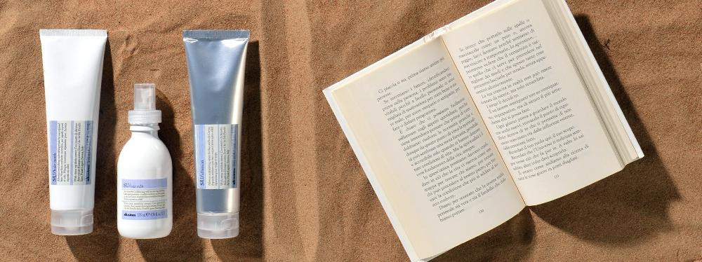 Davines Su products at the beach with a book