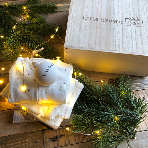 The Little Brown Box limited edition Christmas box, featuring a festive sleepsuit, a board book and a ceramic bauble