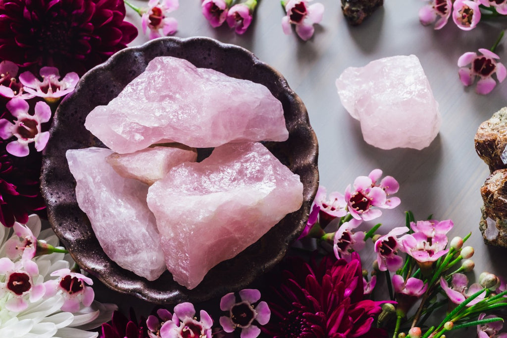 A basin full of rose quartz surrounded with flowers.