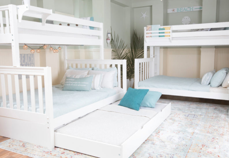 White twin over full bunk beds + trundle bed in a beach vacation house