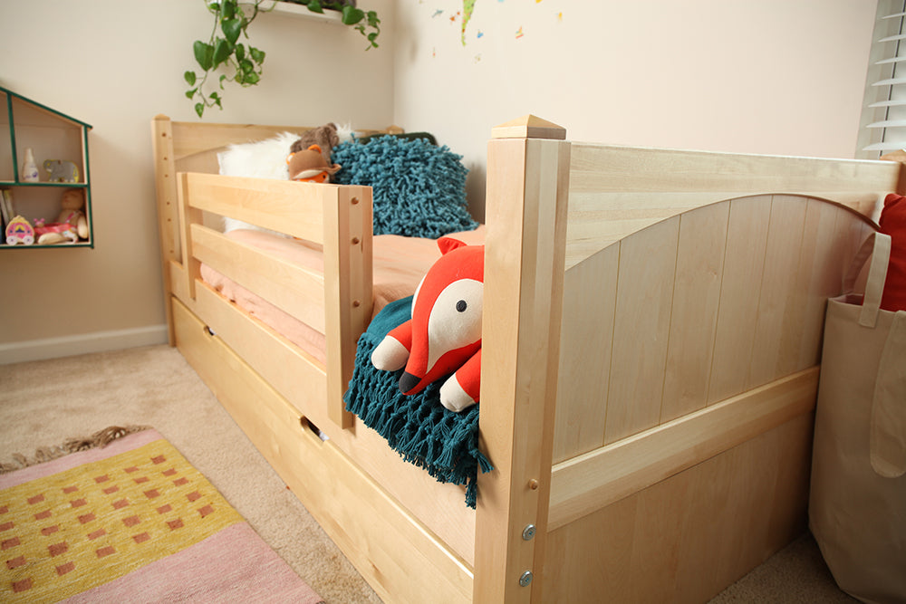 closeup of neutral toddler bed with guardrail light wood
