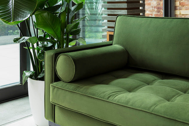 Closeup showing inner corner of a green sofa's arm and back