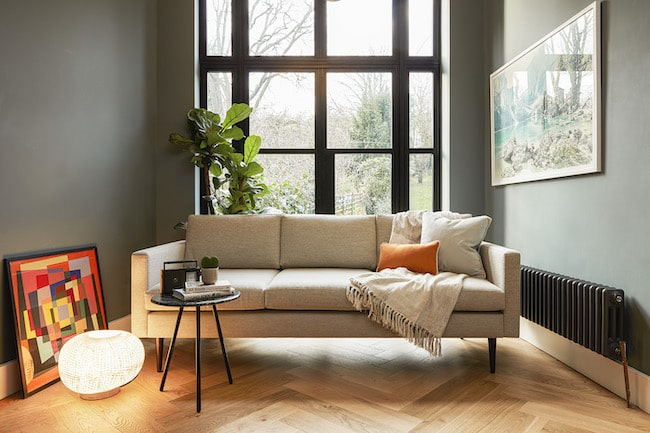 Grey sofa in living room by window with lamp