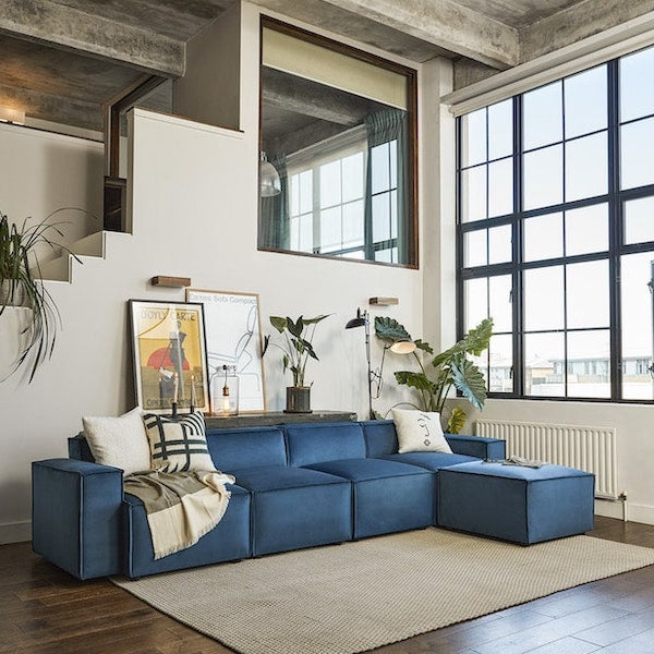 Blue L-shaped sofa in living room by window