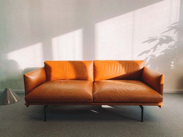 Brown leather sofa in sunlit room