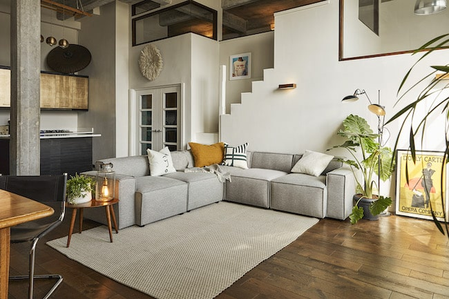 Grey L-shaped sofa demarcating living room from kitchenette