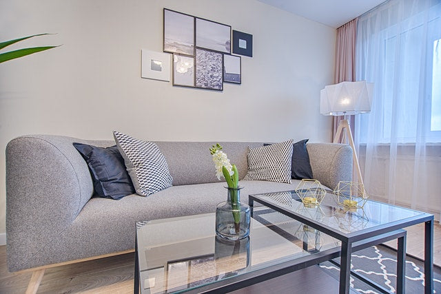 Grey sofa with tuxedo arms and glass table