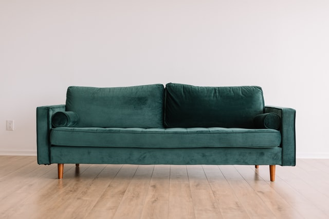 Teal sofa with track arms on wooden floor
