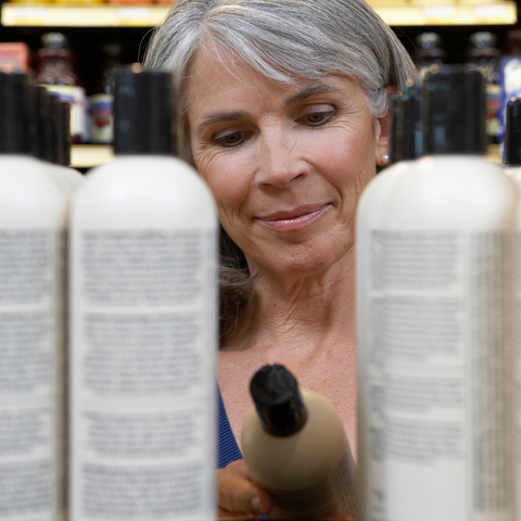 Gray haired women reading labels of bottles in store