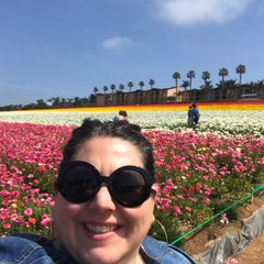 woman in denim jacket and sunglasses standing in a field of multi colored roses