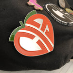 CIB logo peach pin on a bag with other pins