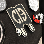 Silver and Black Popsicle pin with CIB logo on black background with other pins