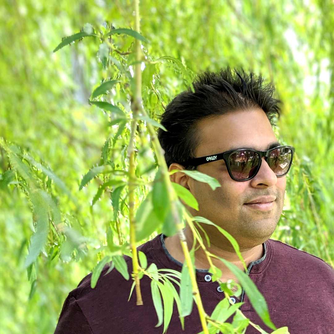 Vickram smiling behind some foliage.