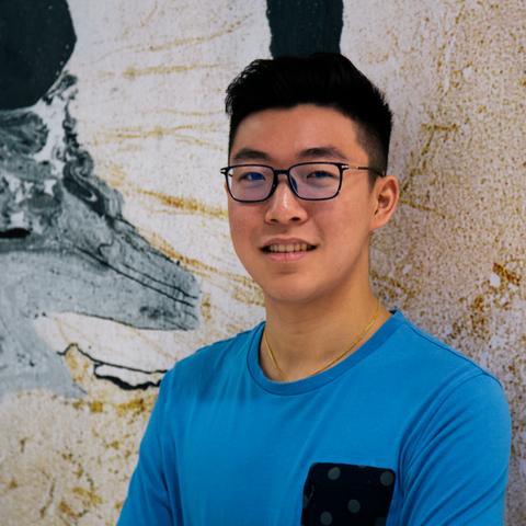 Portrait of smiling Alexander Lee, marketing student, against wall.