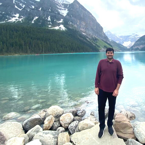 Darshan standing in front of lake and mountains.