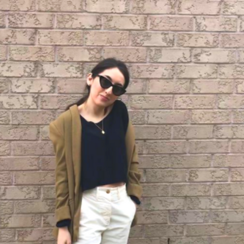 Gabby smiling in sunglasses in front of brick wall.