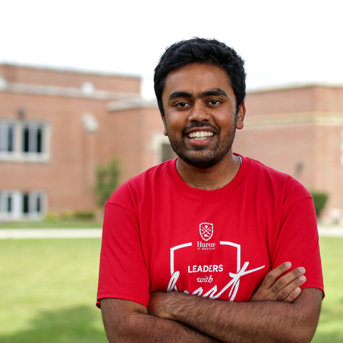 Smiling Jash with arms crossed at campus.