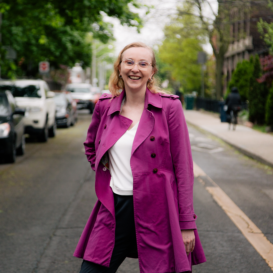Portrait of smiling Liz standing in the street .