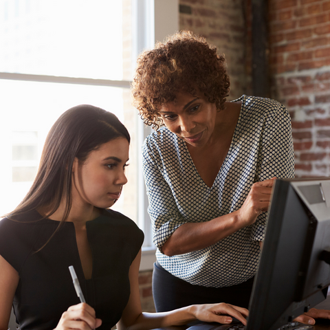 Woman standing over woman at laptop providing help.