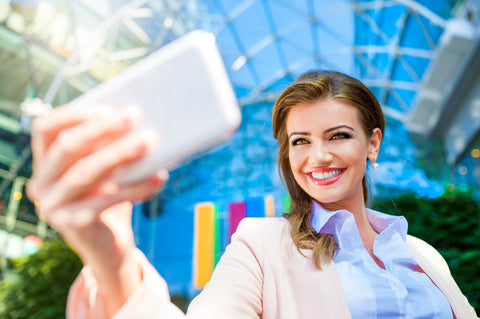Young professional woman smiling and taking picture on mobile phone.