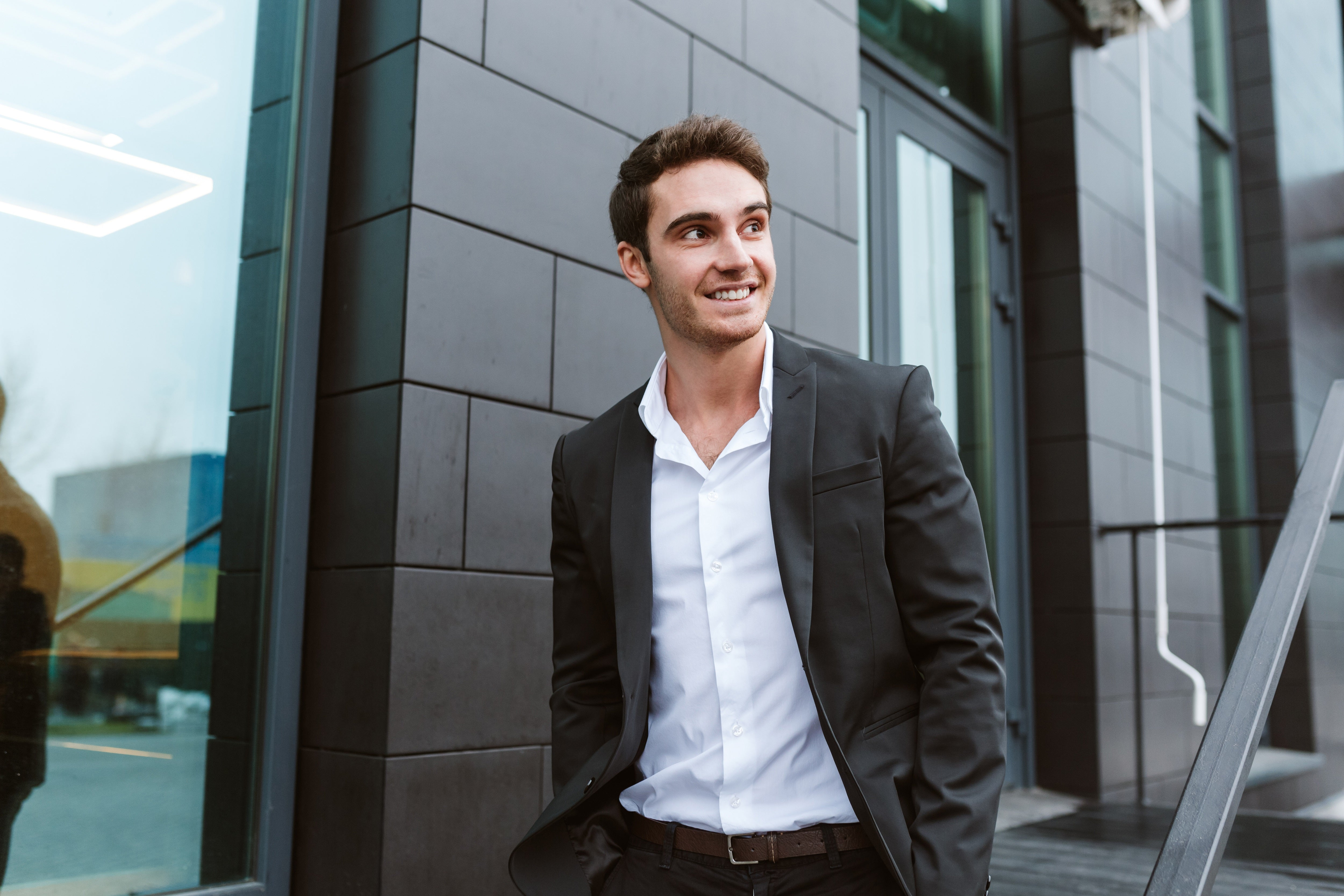 Smiling business man in suit standing outside office entrance.