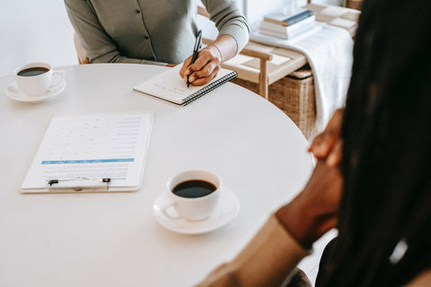 Table holding two cups of coffee with open notebook being written in.