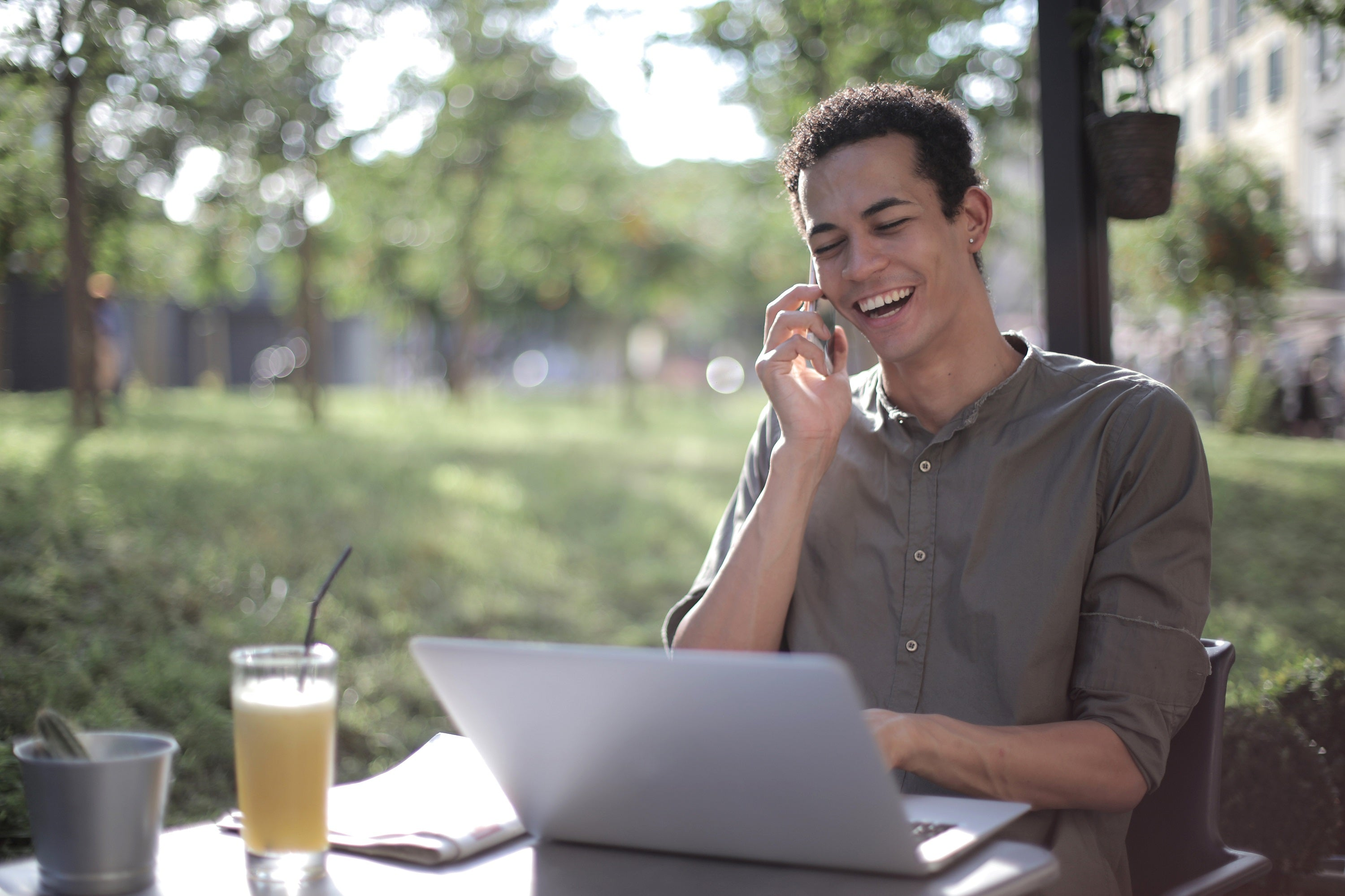 Smiling young professional on the phone in front of laptop.
