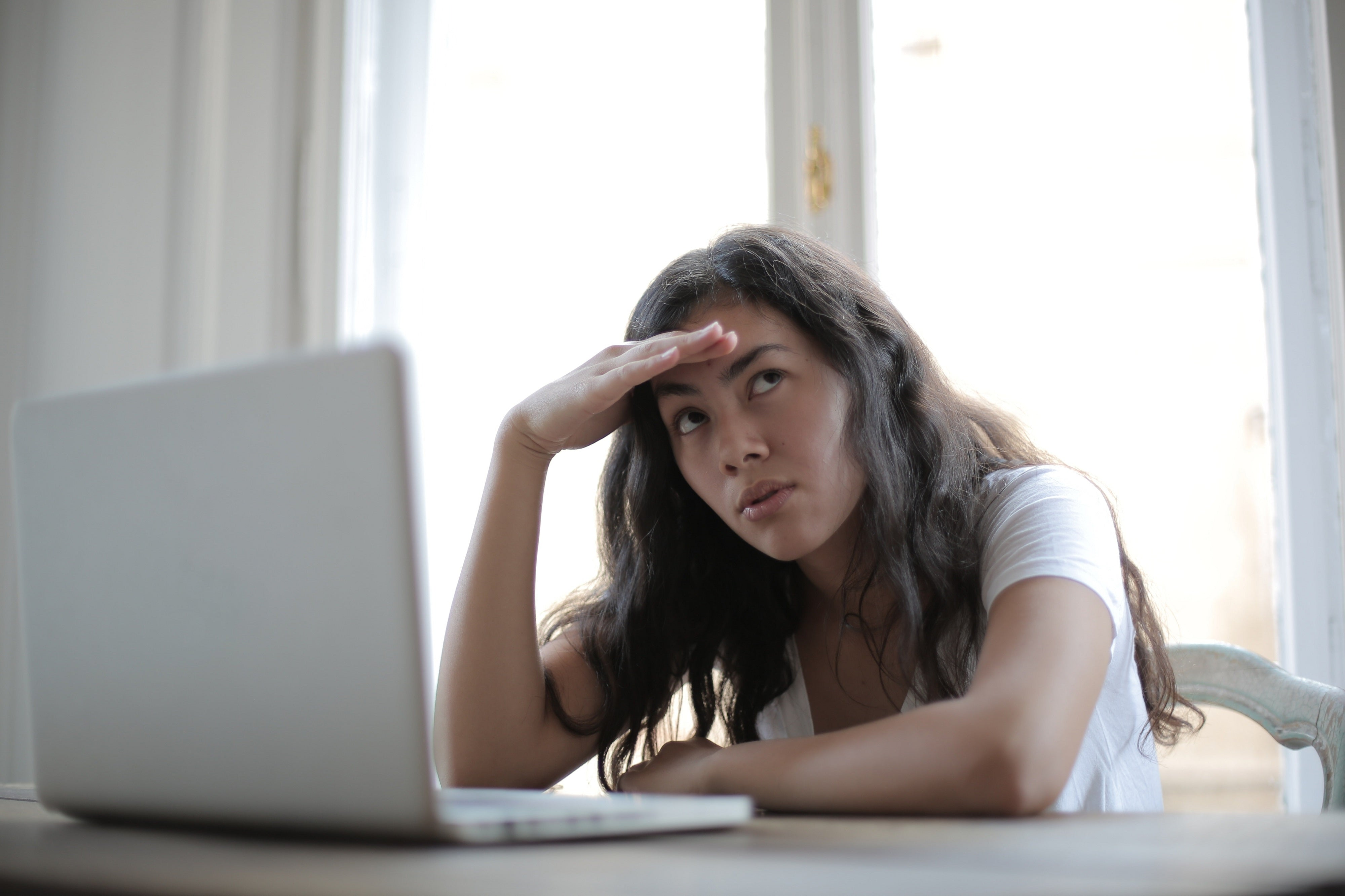 Frustrated young person sitting in front of laptop.