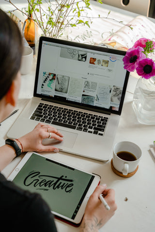 Young professional creating design on tablet in front of laptop.