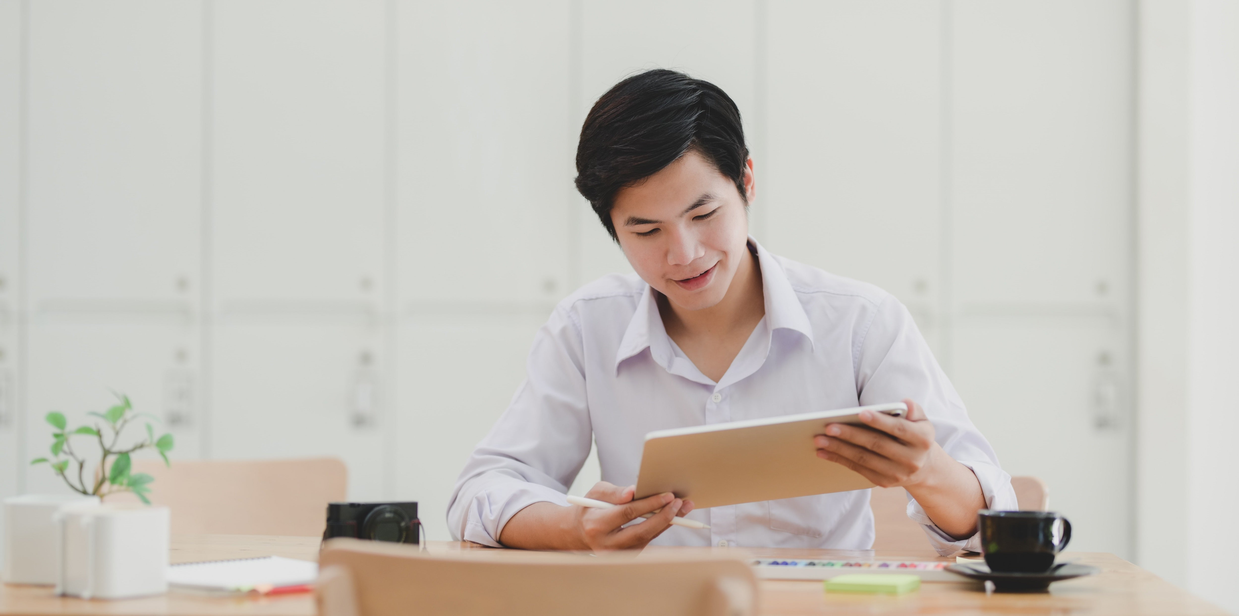 Young man studying tablet at desk.