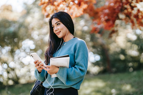 Young female student holding notebook and phone in hand with headphones.