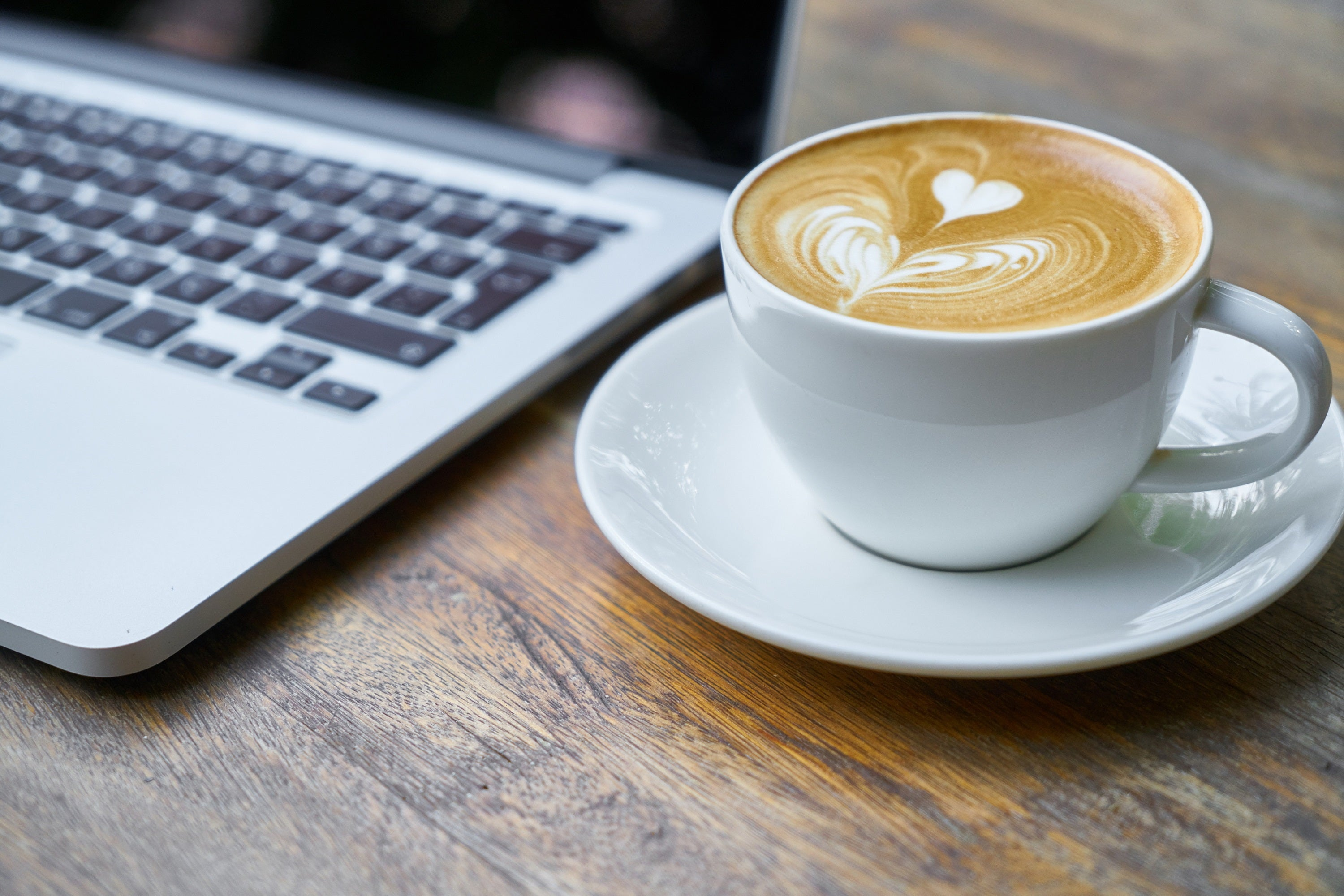 A latte cup beside a laptop.