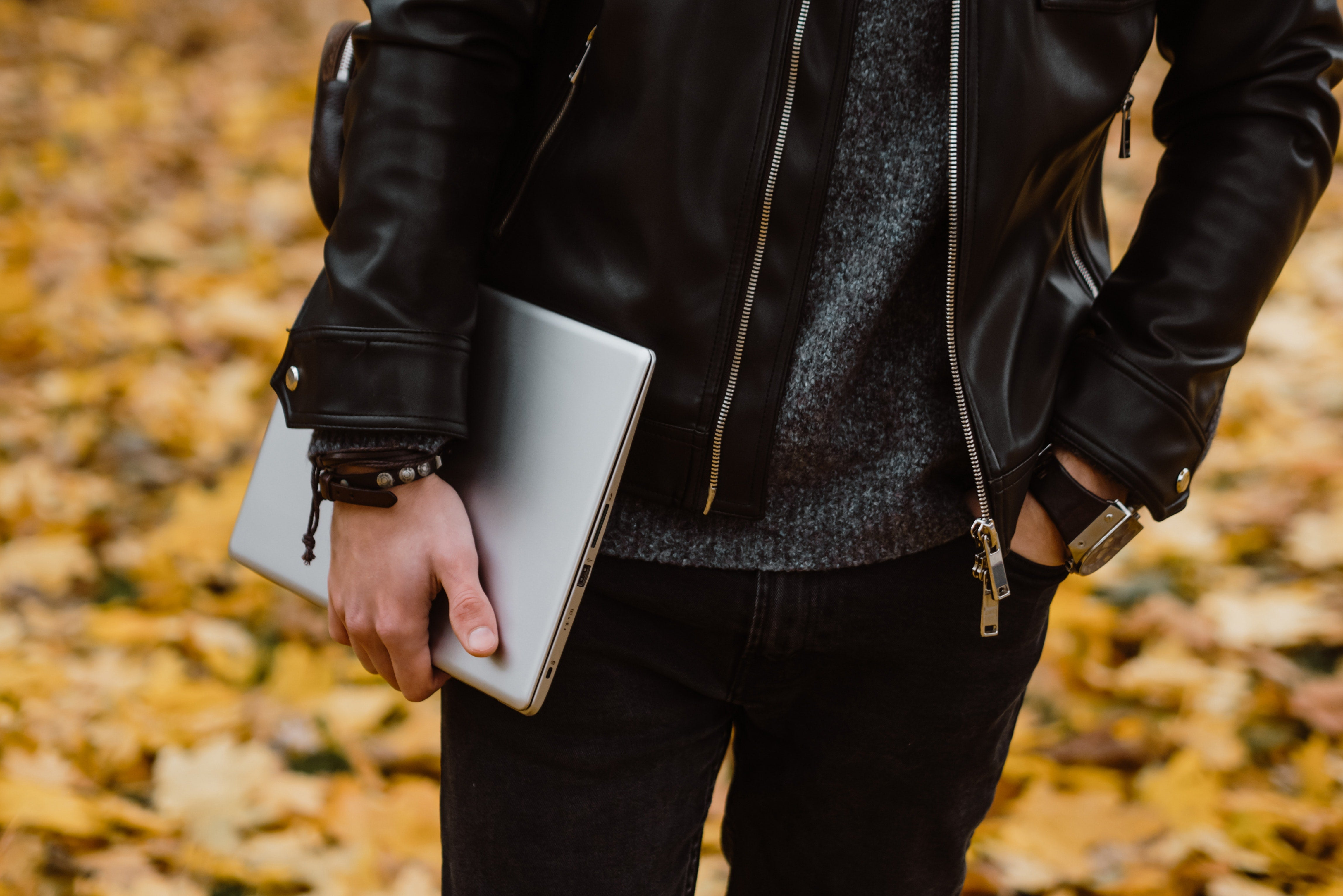 Young man holding laptop under arm outside on a fall day.