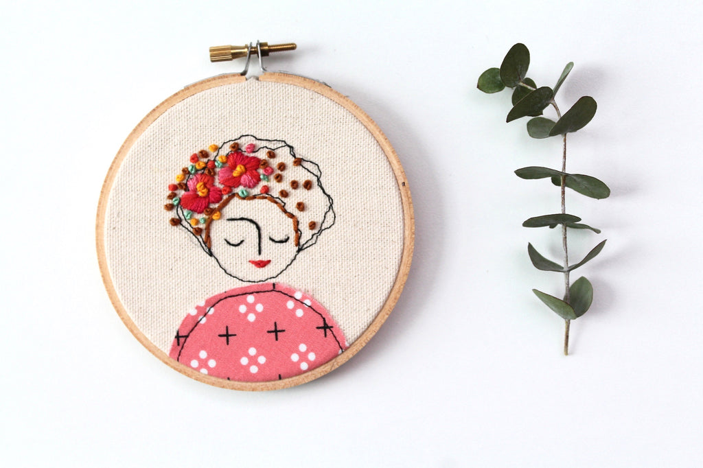 Embroidery of a woman in pink with camellias in her hair