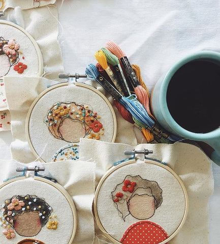 Unfinished embroidery hoops on a table next to embroidery floss and a cup of coffee
