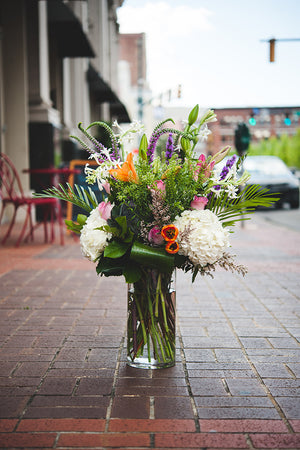 Blue Ivy Flowers - Grand Seasonal Boquet in glass vase on sidewalk