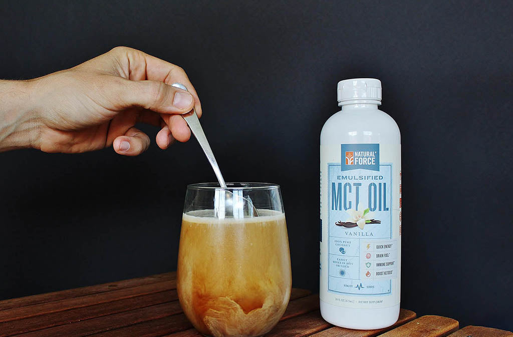 Natural Force creamy MCT Oil being stirred into a glass of coffee