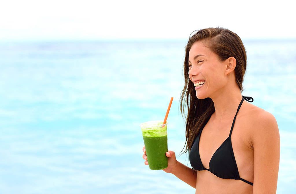 woman in a bikini smiling drinking a marine collage smoothie at the ocean