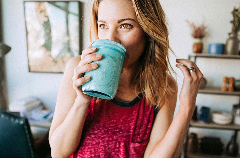 athletic woman drinking a low carb protein shake
