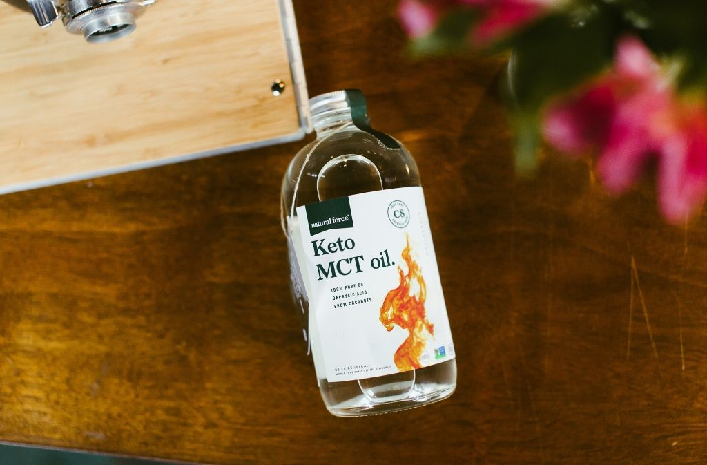 bottle of natural force keto mct oil on a wood table top beside blurry pink flowers