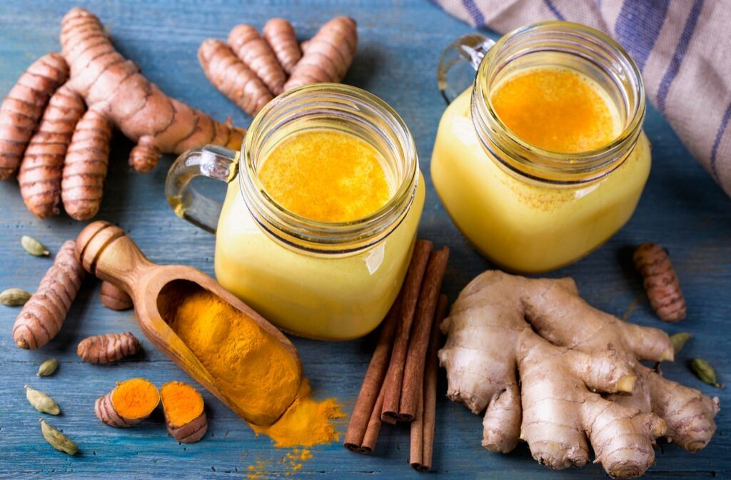 two mugs of turmeric bone broth protein shake surrounded by ginger and turmeric powder