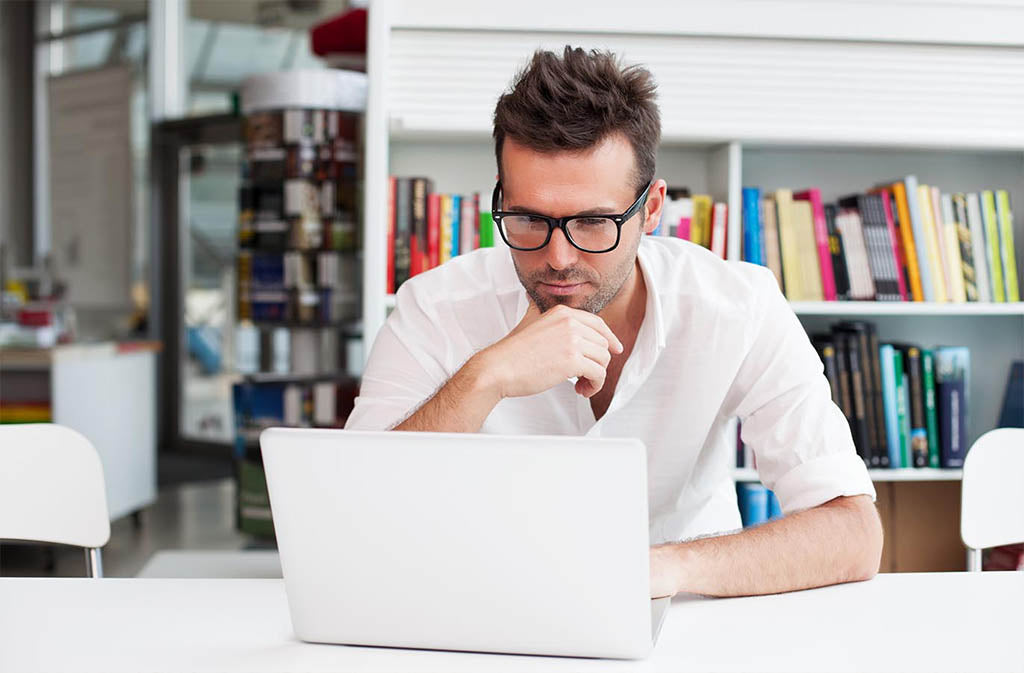 man with glasses looking at a laptop screen