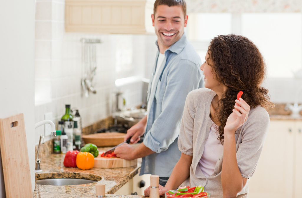 man chopping vegetables in kitchen while smiling at woman who is looking back at him